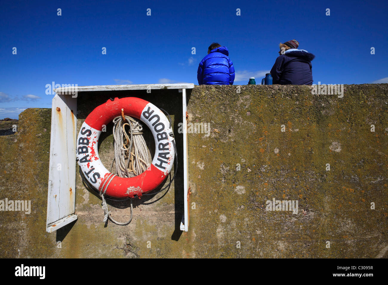 A couple of visitors take a break on the harbour wall at St. Abbs. - Stock Image