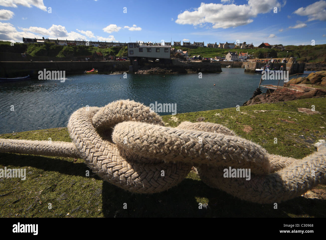 A heavy rope on the harbour wall at St.Abbs. - Stock Image