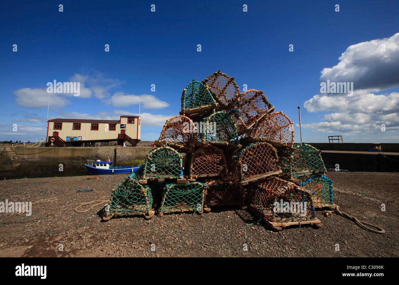The lifeboat station and creel pots on the harbour wall at St. Abbs. - Stock Image