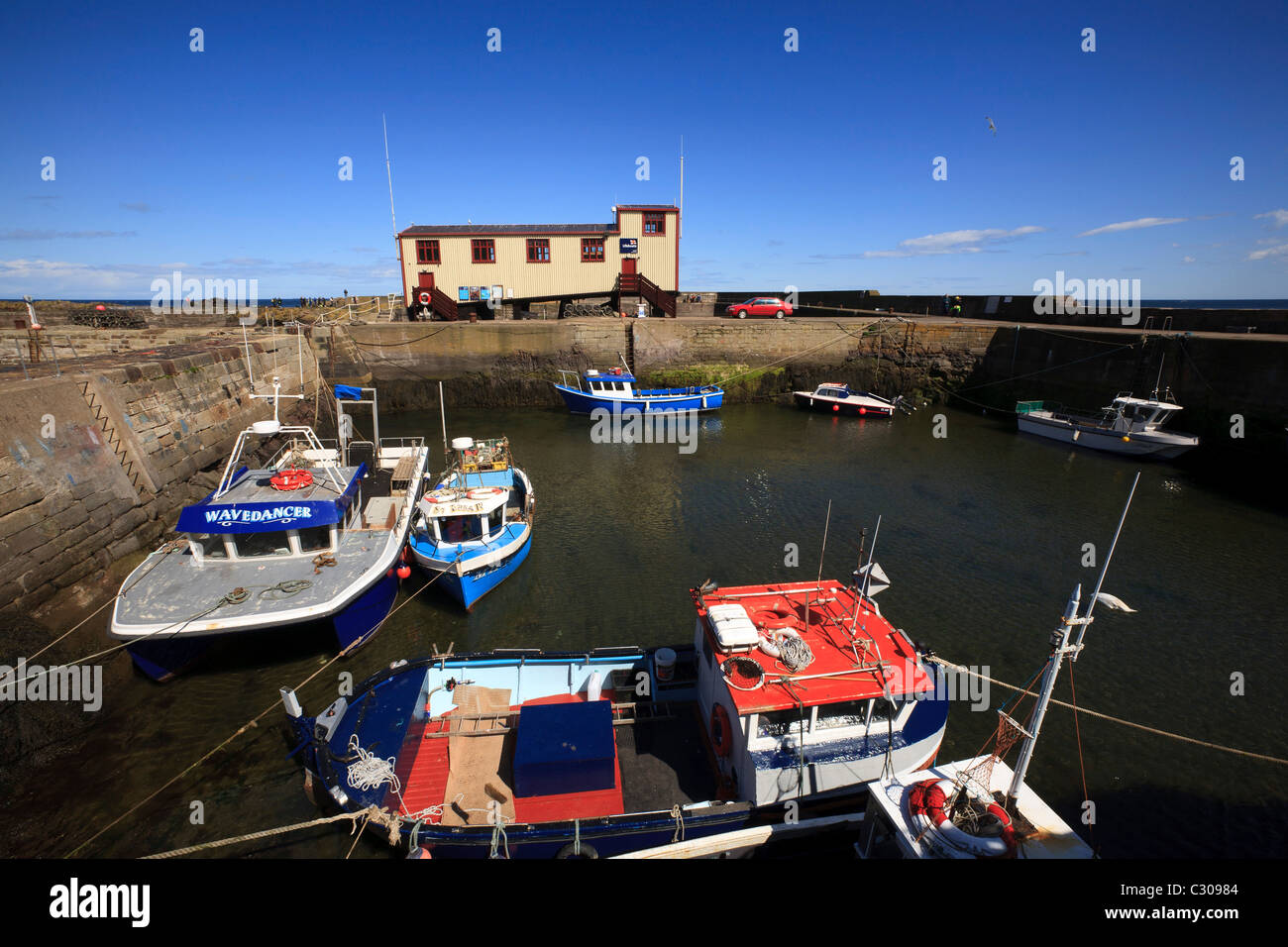 The lifeboat station and boats in the harbour at St. Abbs, Berwickshire. - Stock Image