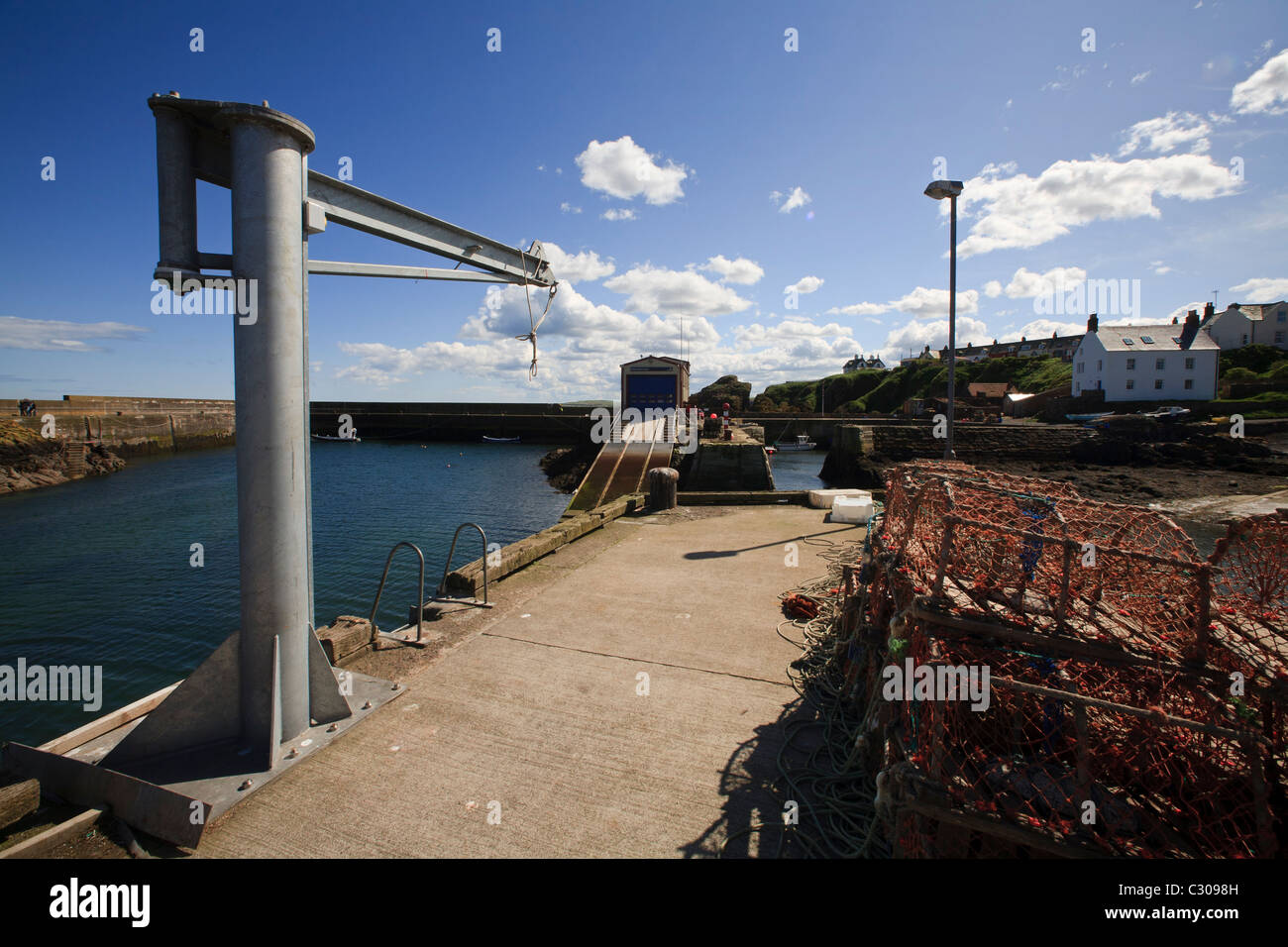 Creel pots and crane on the harbour wall at St. Abbs, Berwickshire - Stock Image