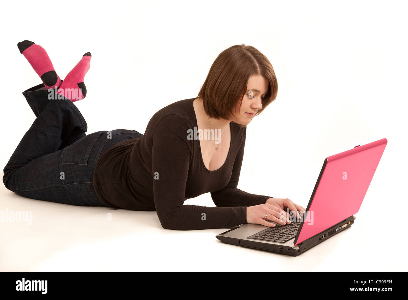 A young woman in her twenties lying on a white back ground using a laptop - Stock Image