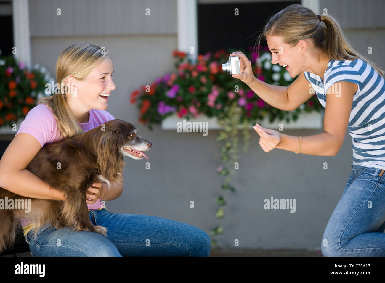 Teen girl poses with her dog while best friend takes photo with digital camera - Stock Image