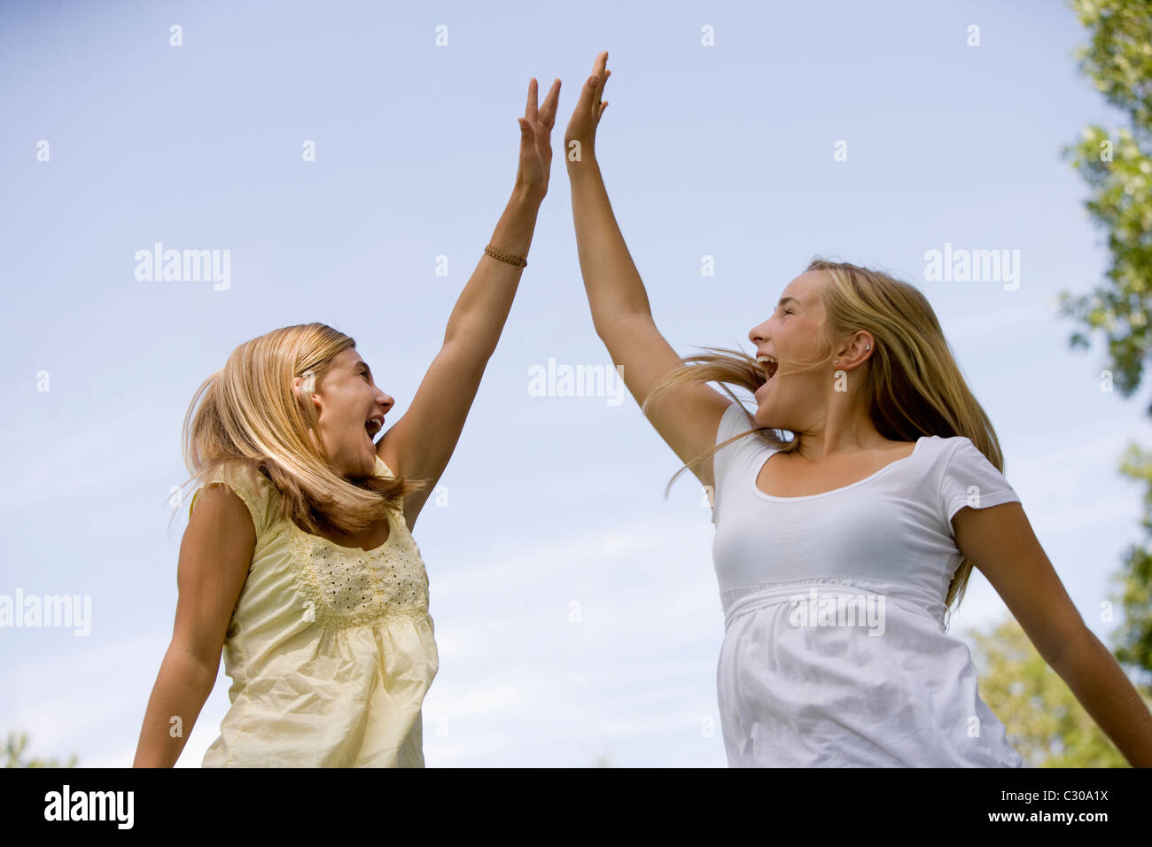 Teen girls celebrate winning by jumping in air and doing a high-five Stock Photo