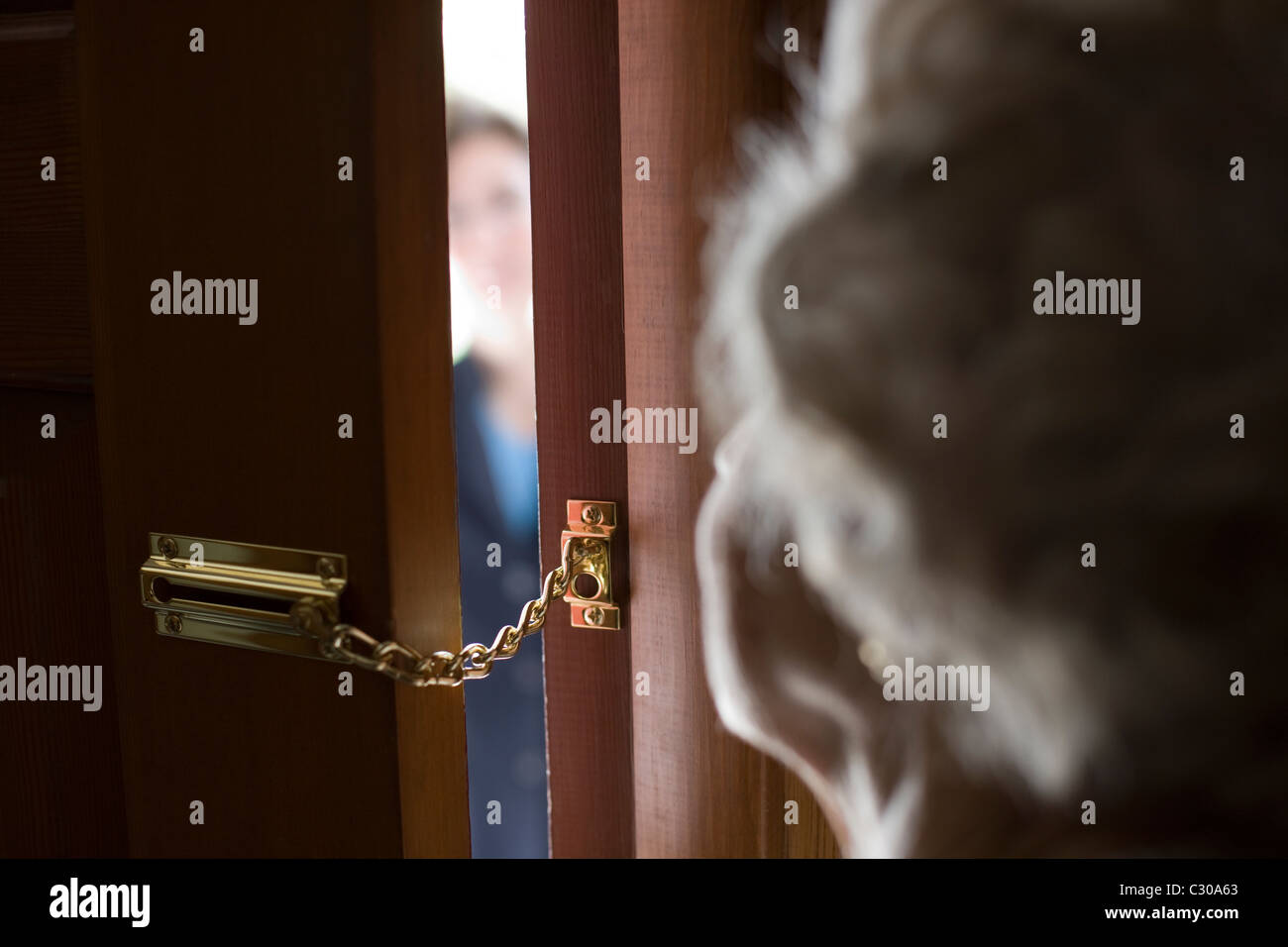 Senior woman using a security chain on front door - Stock Image