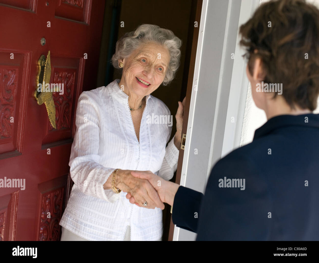 Smiling senior woman greeting visitor at the front door - Stock Image