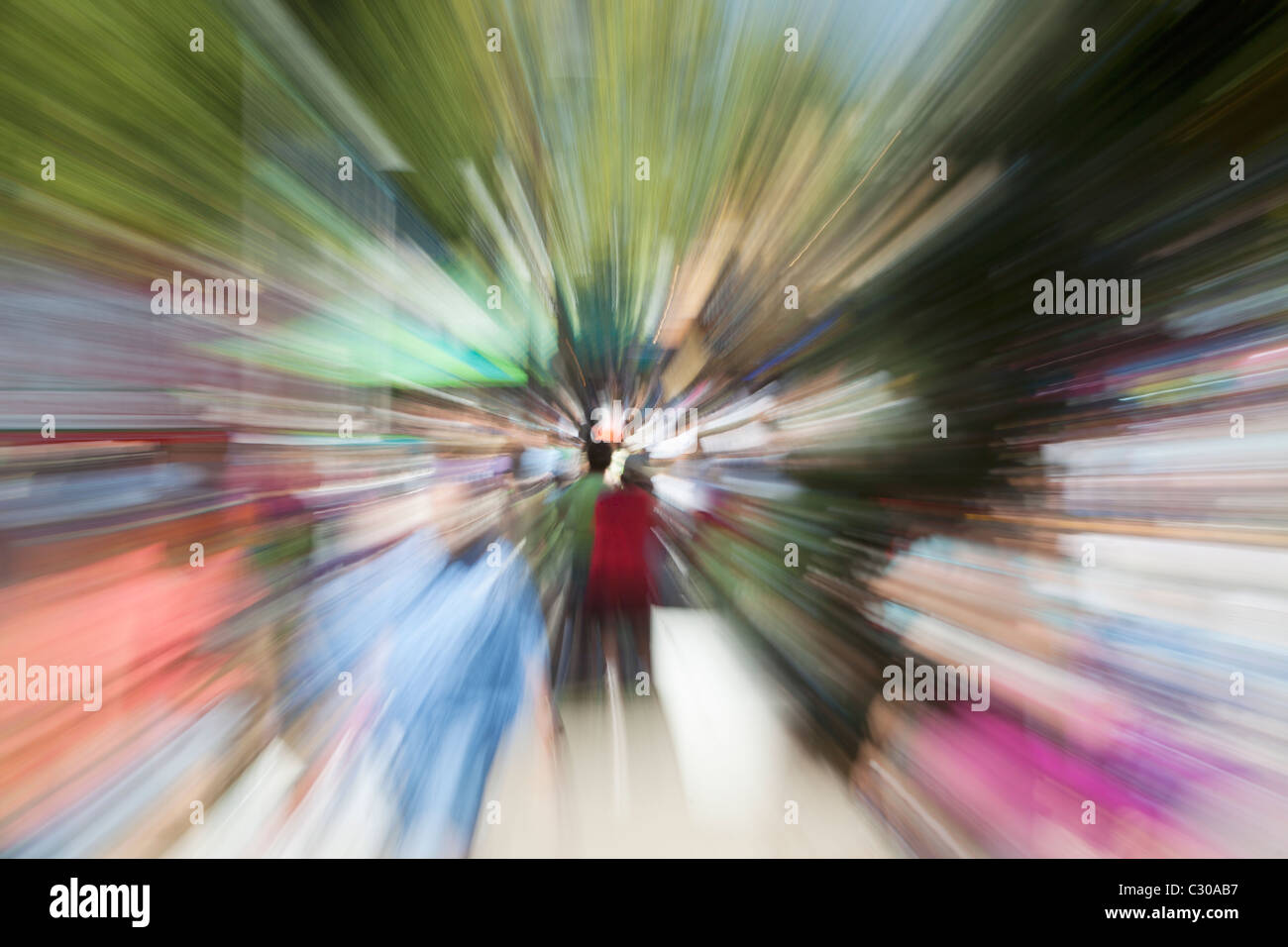 Motion blurred zoom of crowd of people walking - Stock Image