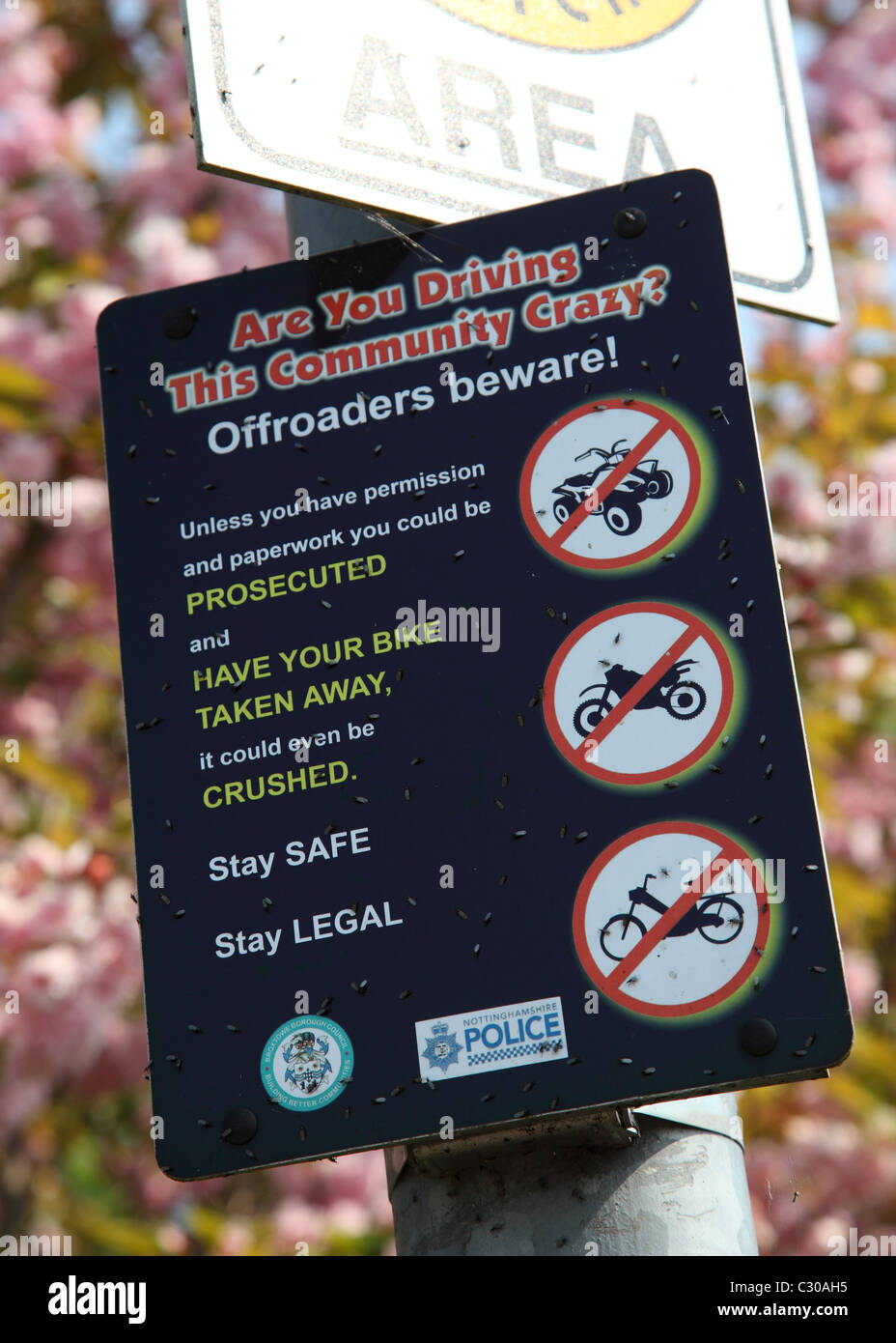 A police sign warning illegal offroad vehicles will seized and crushed. - Stock Image