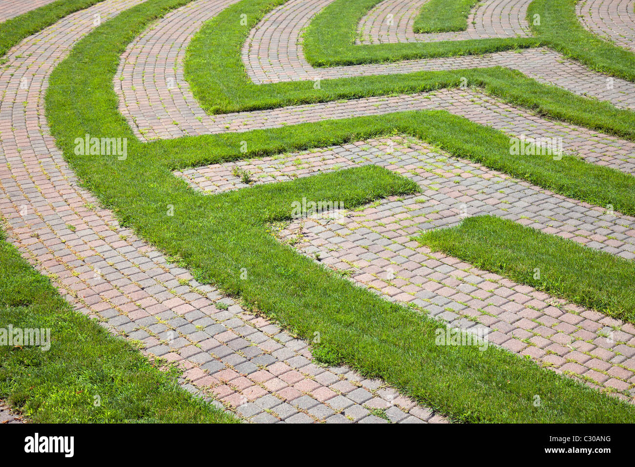 Park maze with a cobblestone walkway and grass boundaries. Horizontal shot. - Stock Image