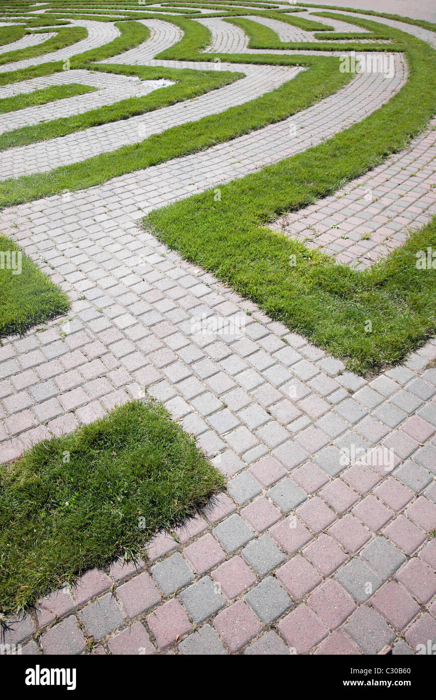 High angle view of the beginning of a maze with a cobblestone walkway and grass boundaries. Vertical shot. - Stock Image