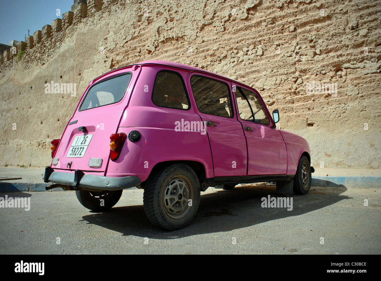 Pink Renault 4 parked outside the medina in Essaouira, Morocco - Stock Image
