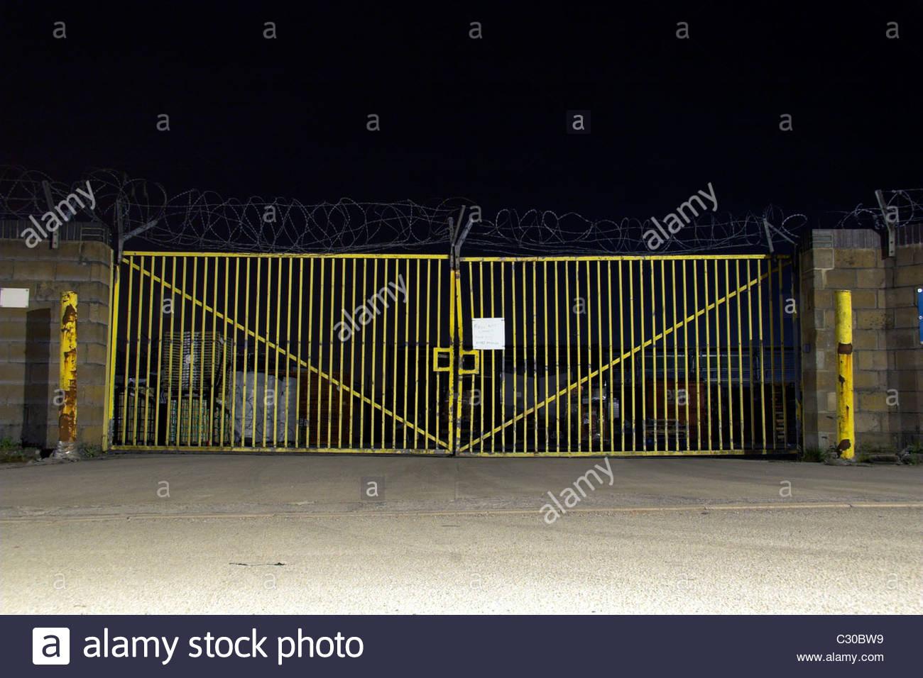 Gated yard at night. - Stock Image