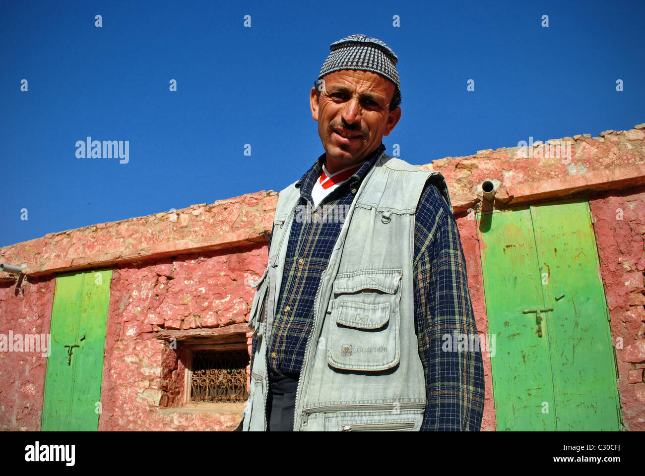 Portrait by colourful wall in Immouzzer, Morocco - Stock Image