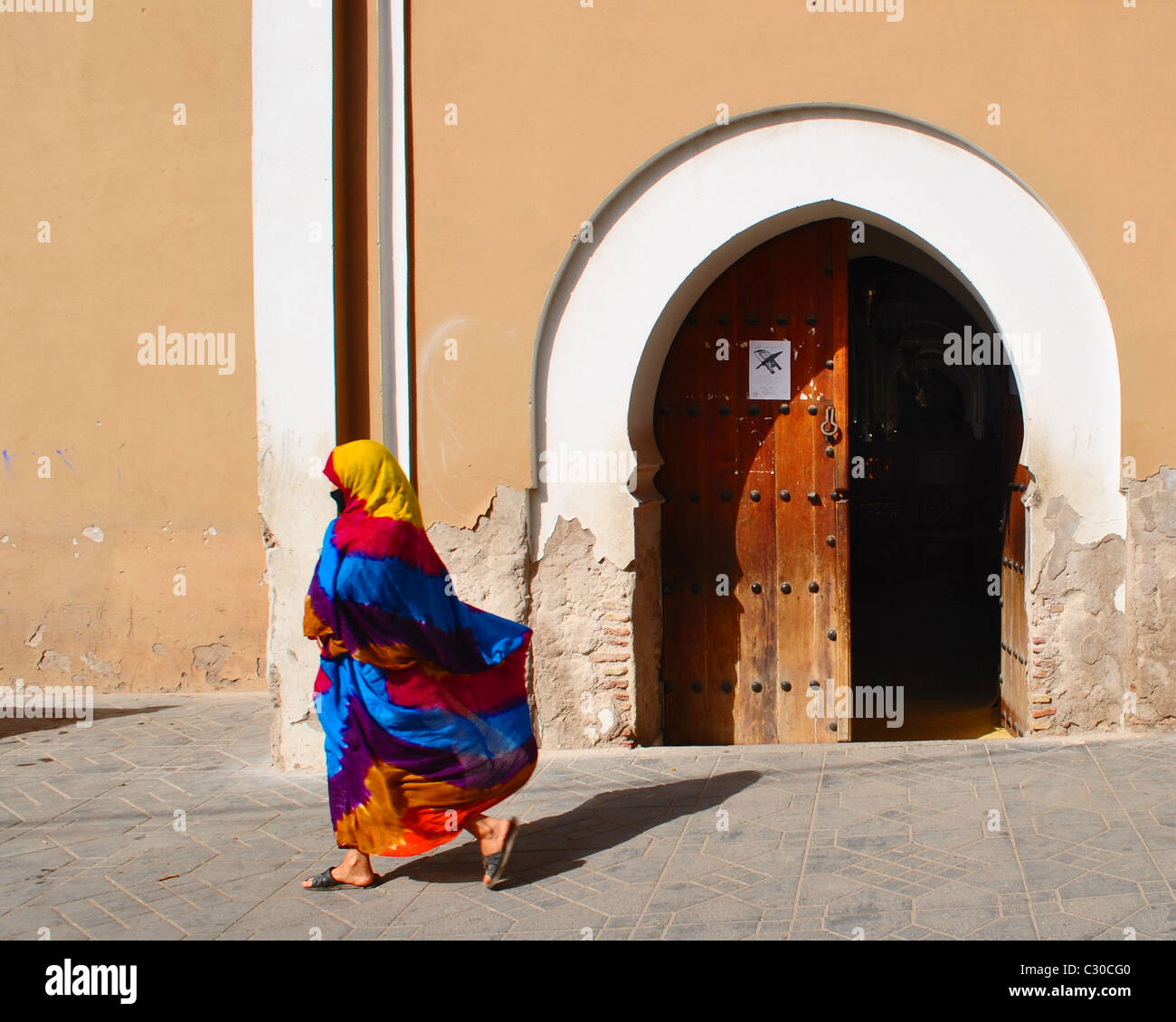 Woman in colourful, flowing jellaba, walking past an open door in Taroudant, Morocco - Stock Image