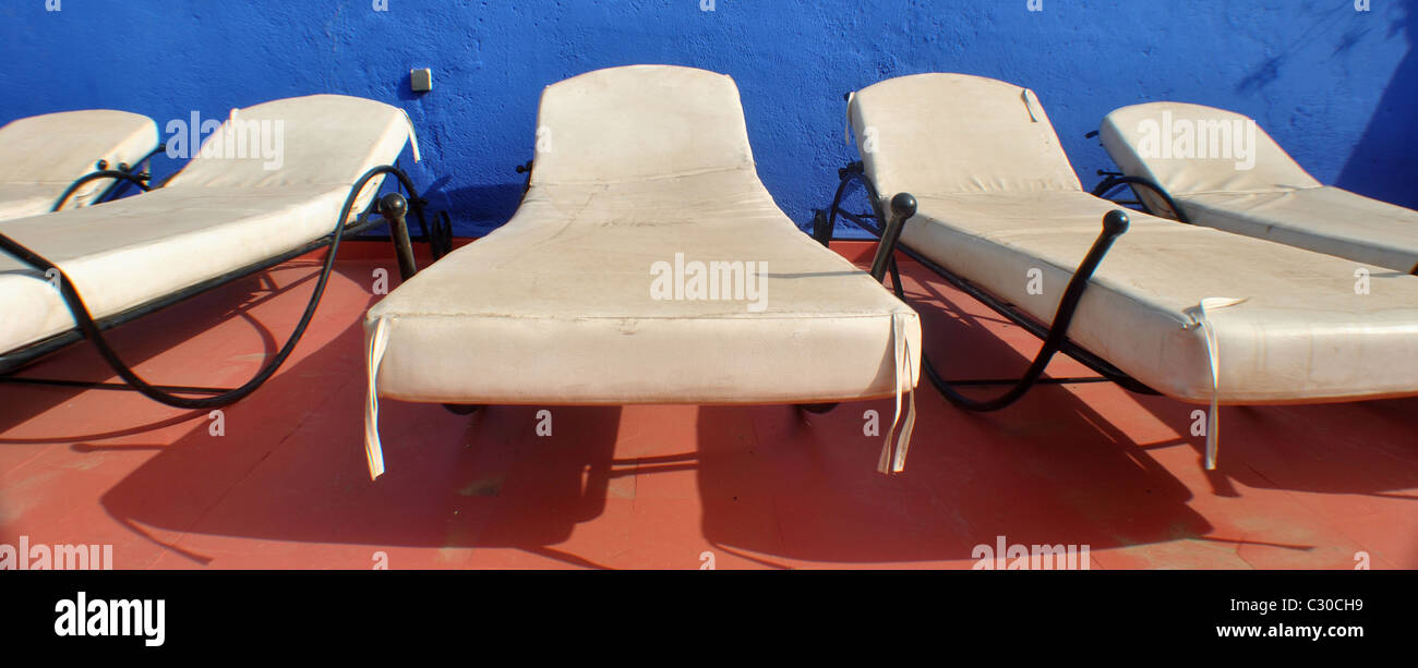 Sun loungers and colourful background - Stock Image