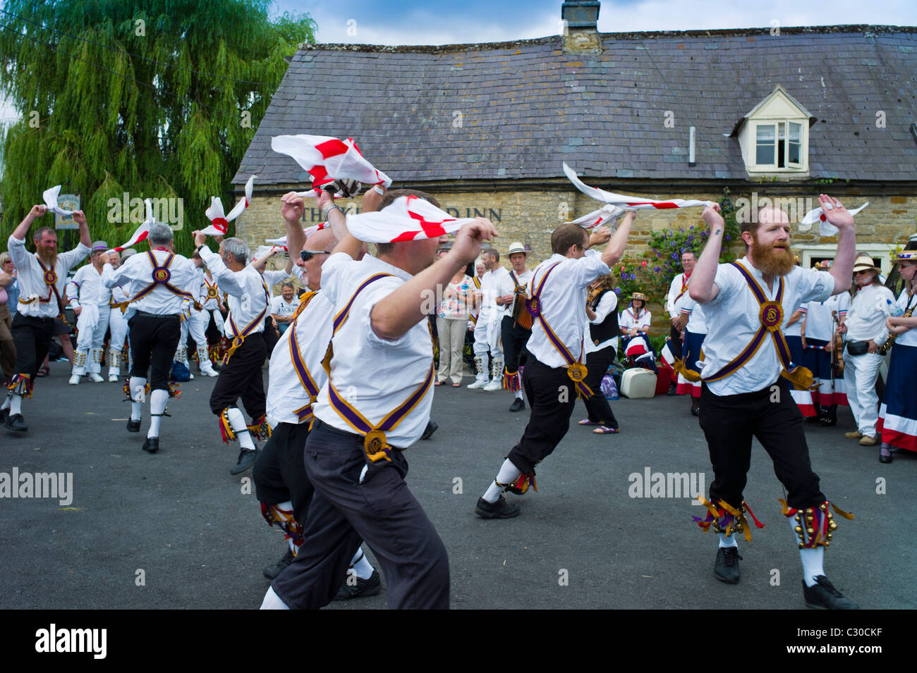 Morris dancers, Brighton Morris Men, perform a dancing display at The Kings Head Pub in Bledington, Oxfordshire, - Stock Image