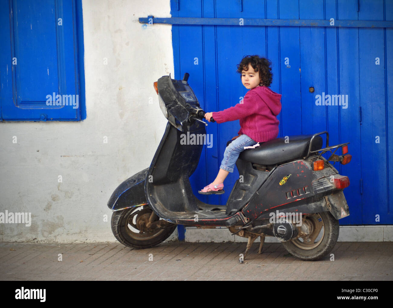 Little girl on scooter - Stock Image