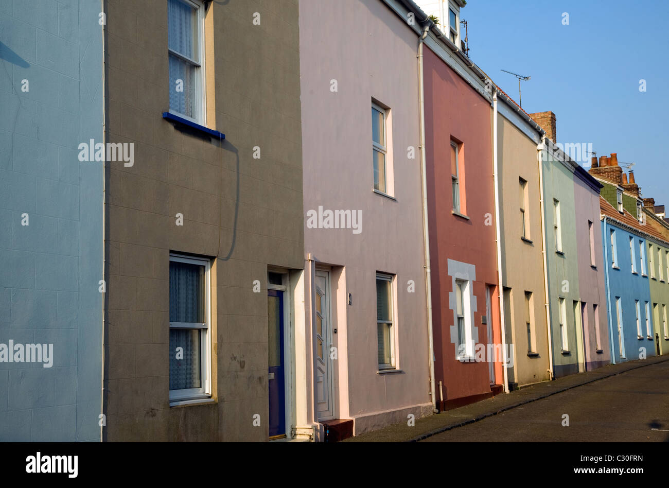 Row terraced housing brightly coloured St Peter Port Guernsey Channel Islands - Stock Image