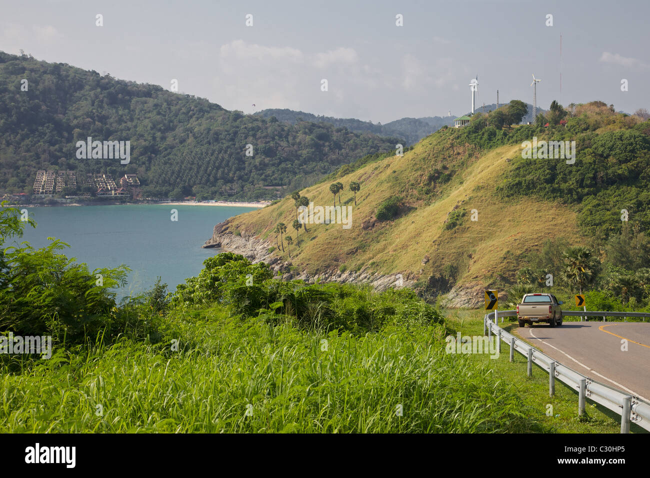 A high shot looking down onto Nai Harn beach with the Royal Yatch club and wind turbines on the hill, Phuket, Thailand - Stock Image
