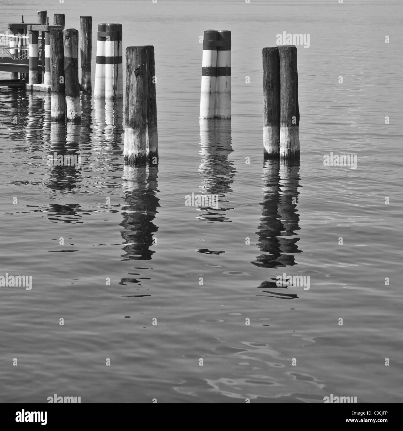 Poles for boats nearby a pier at Iseo Lake in Italy. Stock Photo