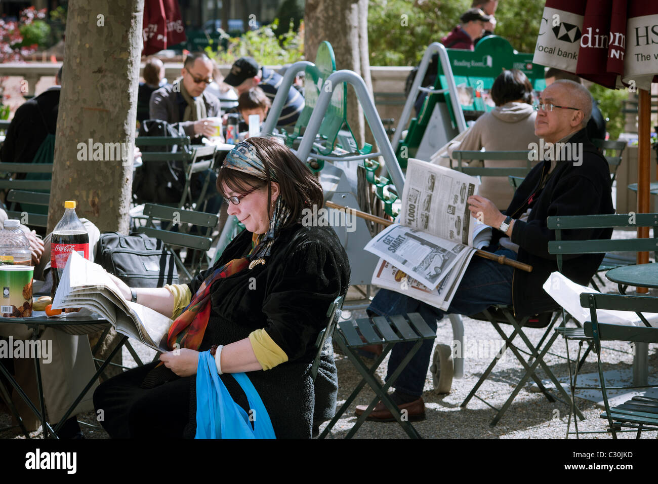 Visitors to Bryant Park in New York take advantage of free newspapers in the Bryant Park Reading Room area of the - Stock Image