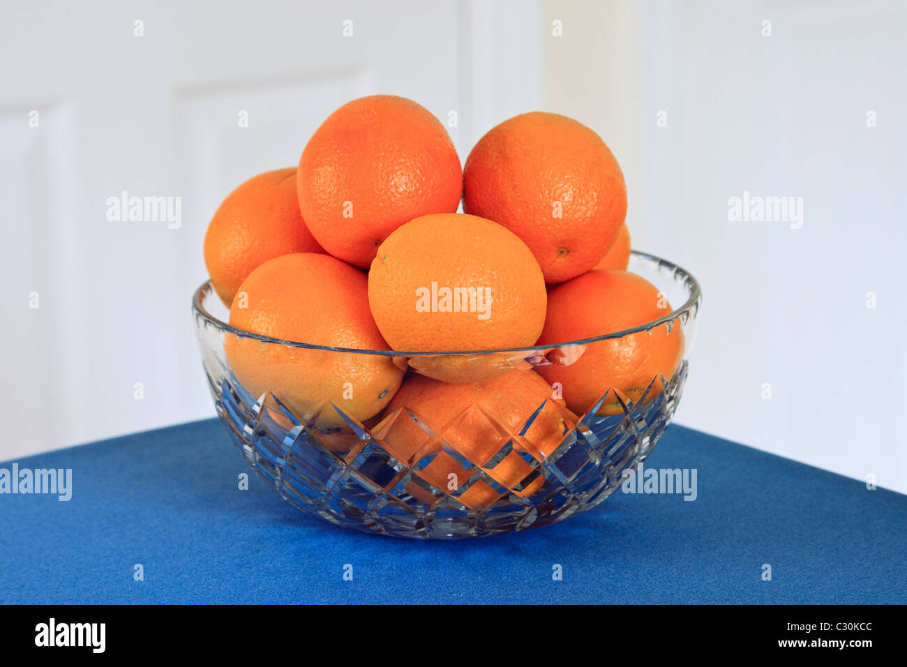 Oranges in a crystal glass fruit bowl on a blue table. UK - Stock Image