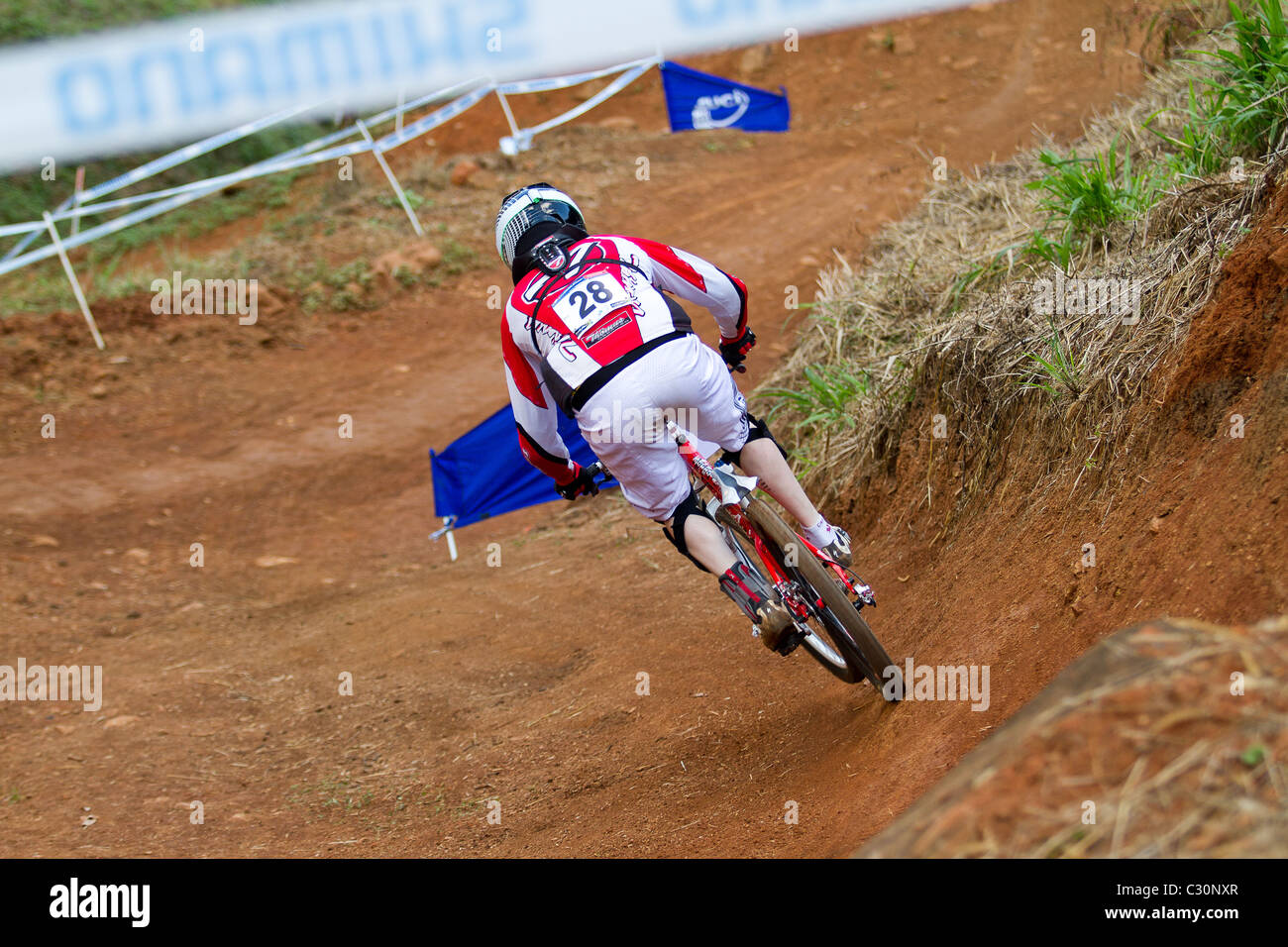 Four Cross rider on practice run through berm at UCI MTB World Cup - Stock Image