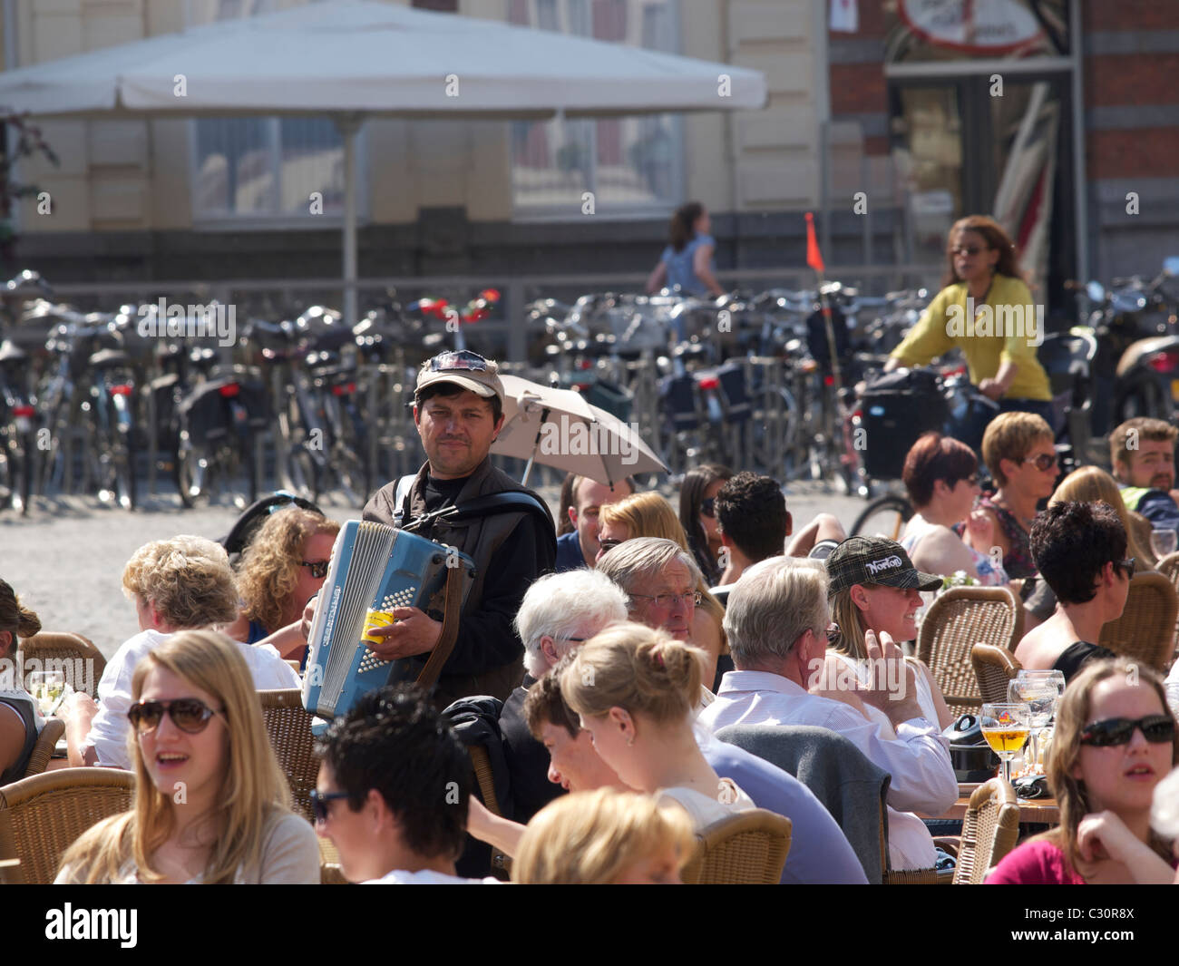 Man playing the accordeon for many people sitting outside in Bergen op Zoom the Netherlands. Stock Photo