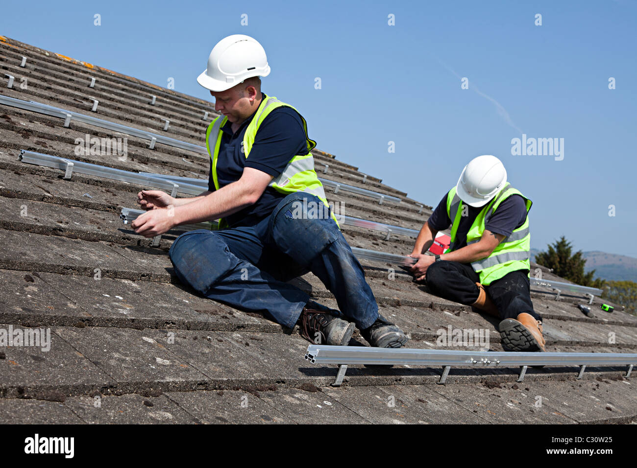 Two men fitting rails for solar pv panel attachment to house roof Wales UK - Stock Image
