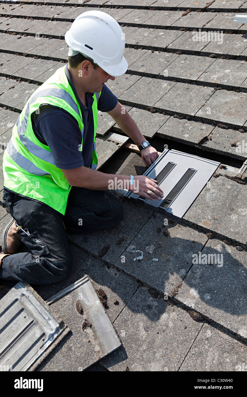 Man fitting ventilation tile in house roof Llanfoist Wales UK - Stock Image