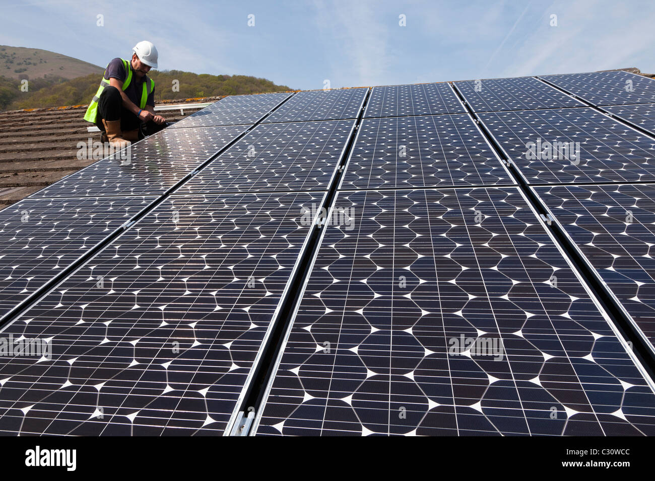 Fitting solar pv panels to a house roof Wales UK - Stock Image