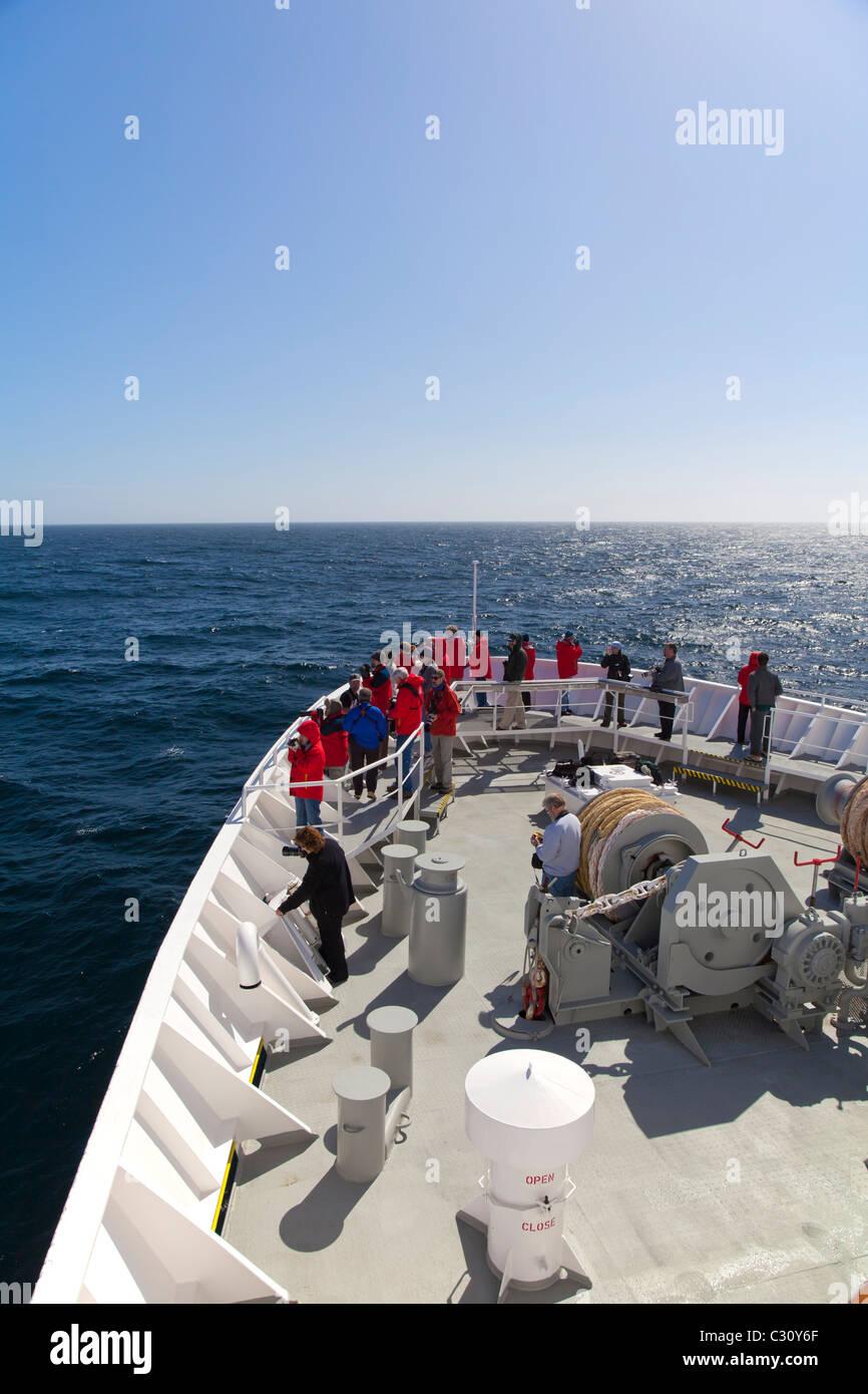 Expedition ship passengers on the deck near Shag Rocks, South Atlantic Ocean - Stock Image