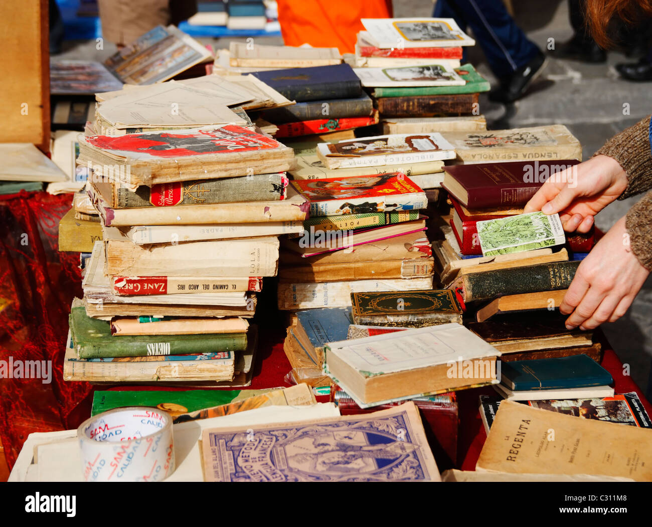 Secondhand books on stall in famous street market in calle Ferria, in barrio Macarena, Seville, Spain, Europe - Stock Image