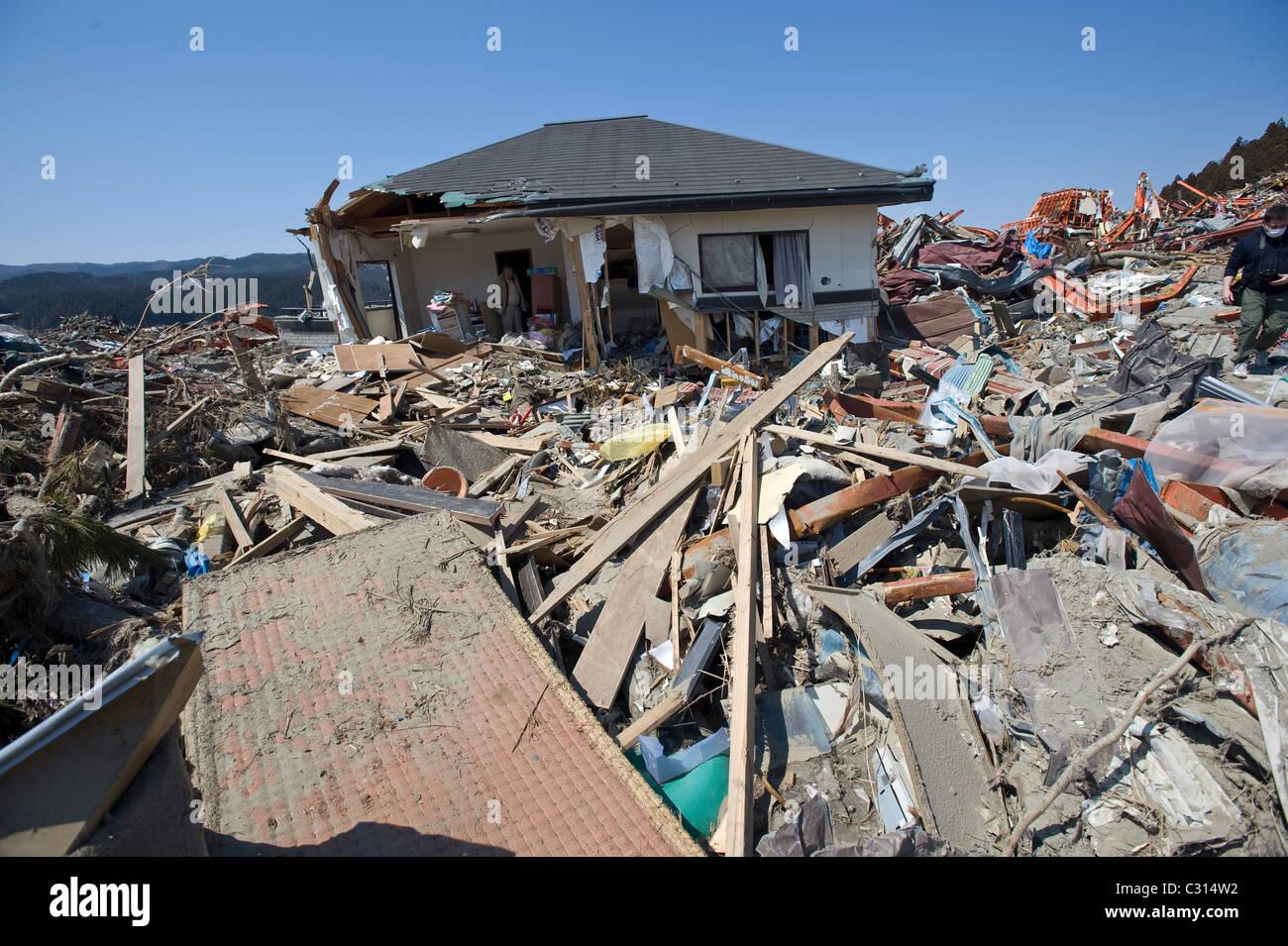 Katsunari Sasaki, 76, looks through the wreckage of his home which was moved 700 meters in Rikuzentakata, Japan - Stock Image