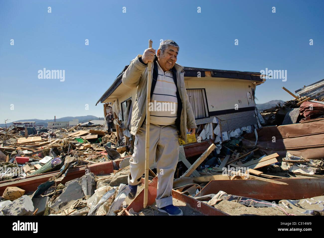 Katsunari Sasaki, 76, looks through the wreckage of his home - Stock Image