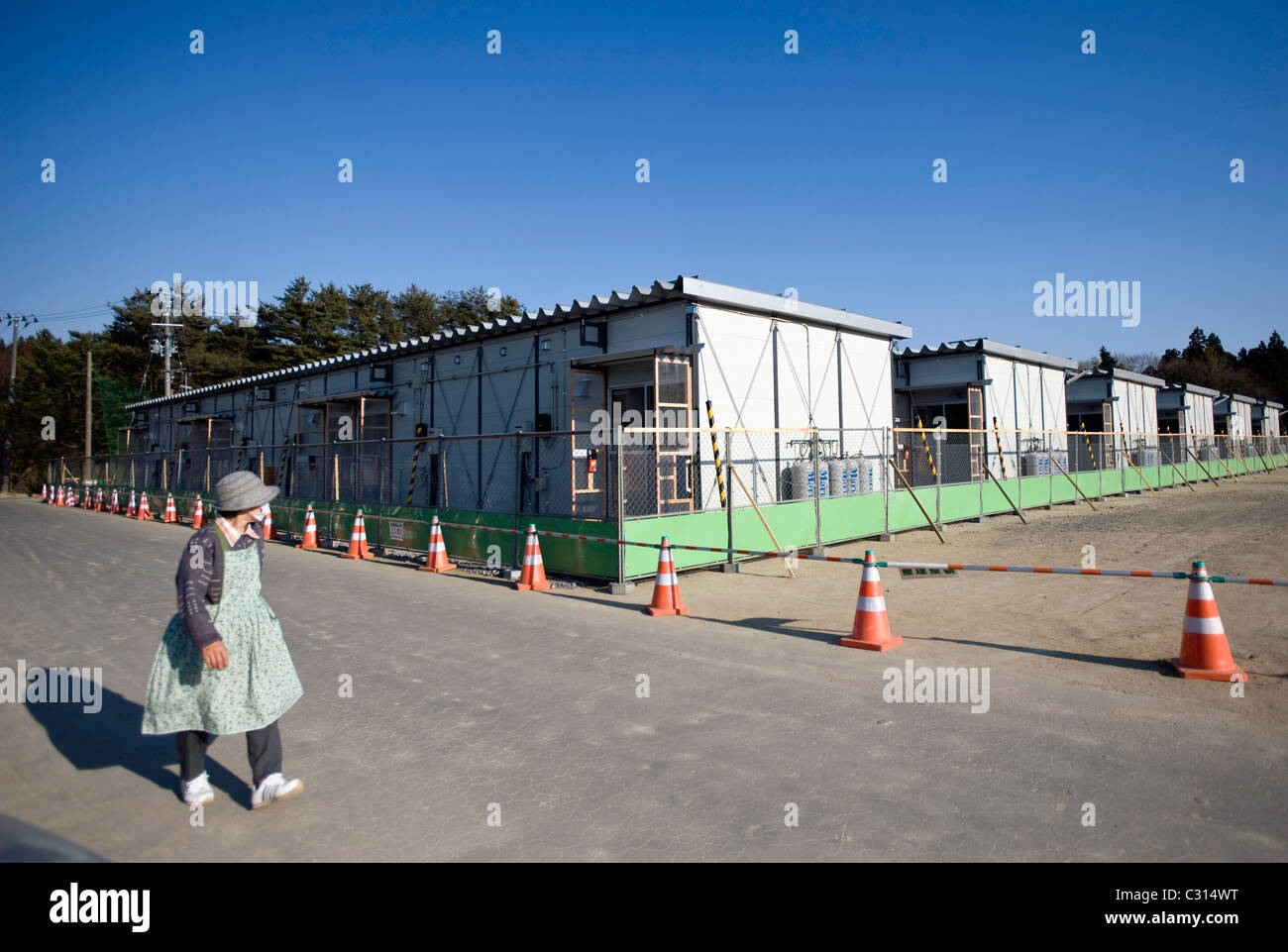 An elderly woman walks past prefab housing set up to accommodate 36 families who lost their homes during the March - Stock Image