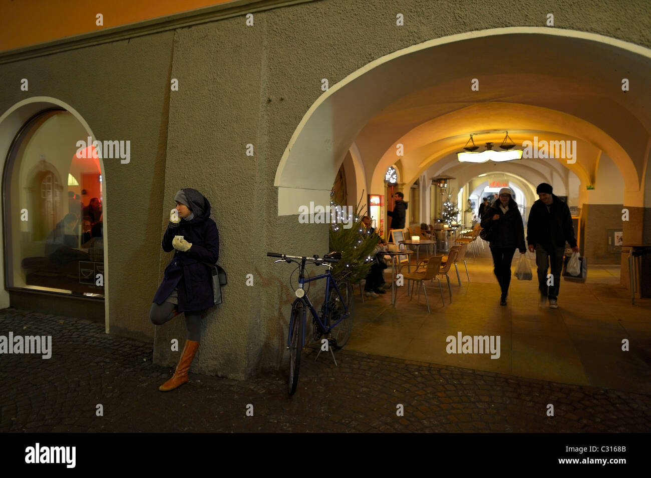 A young woman making a cell phone call outside of a restaurant, Feldkirch, Austria AT - Stock Image