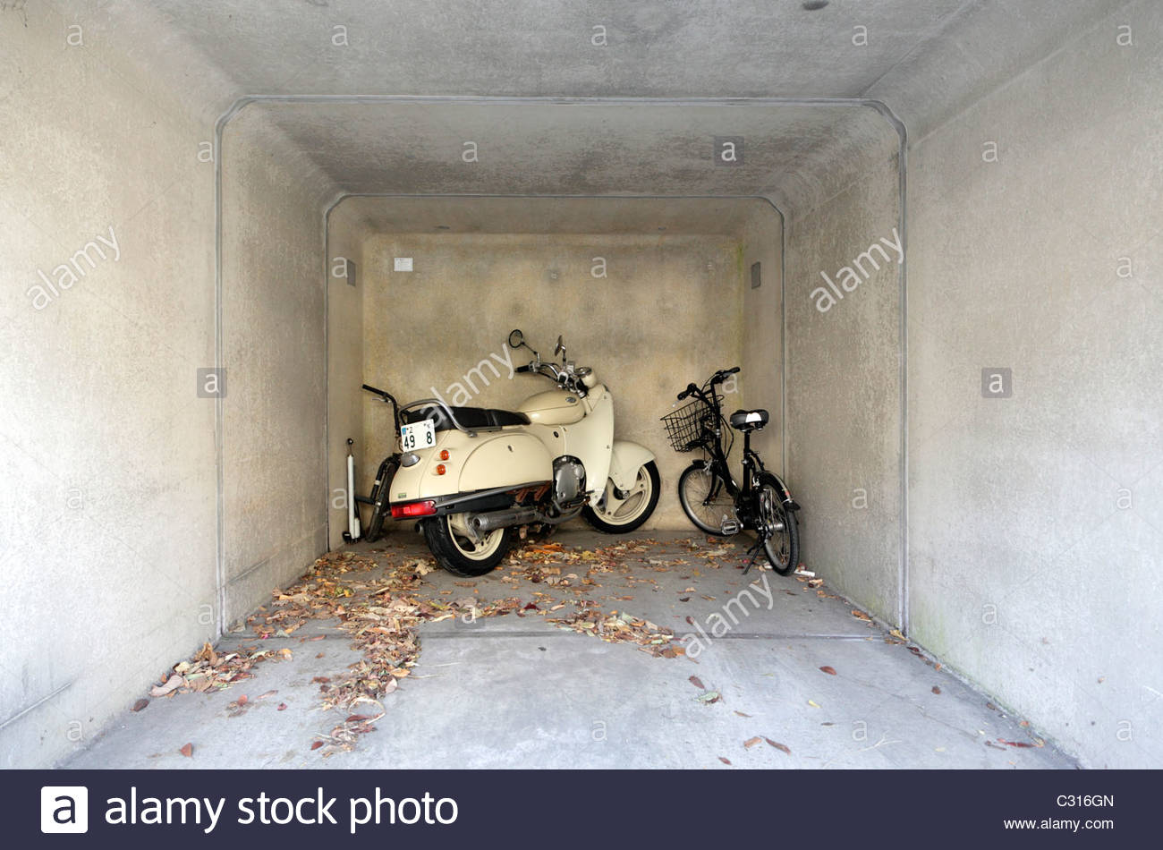 one car parking garage with a bicycle and a motorcycle - Stock Image