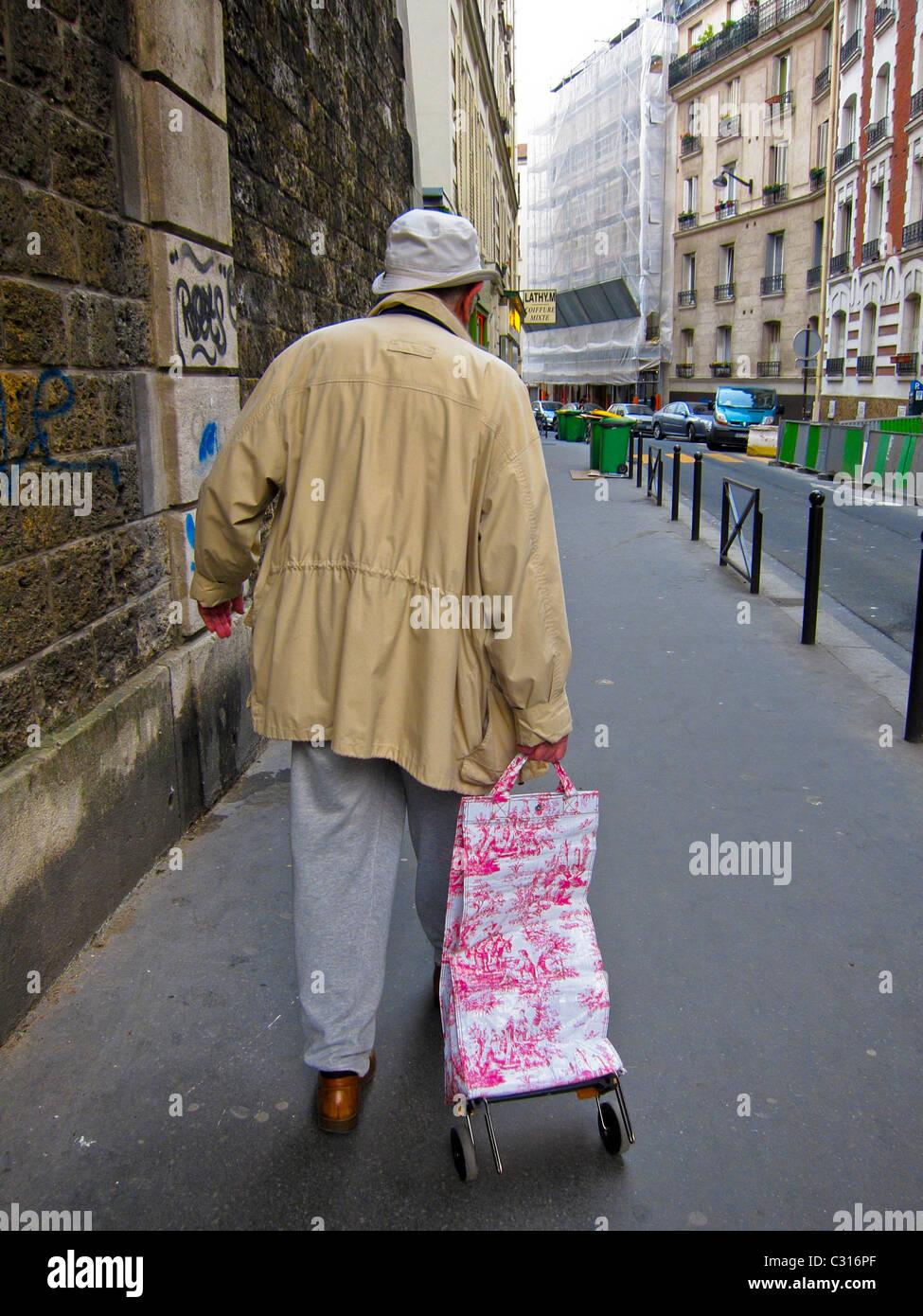 Paris, France, Senior Man Walking Away on Street with Shopping Cart - Stock Image