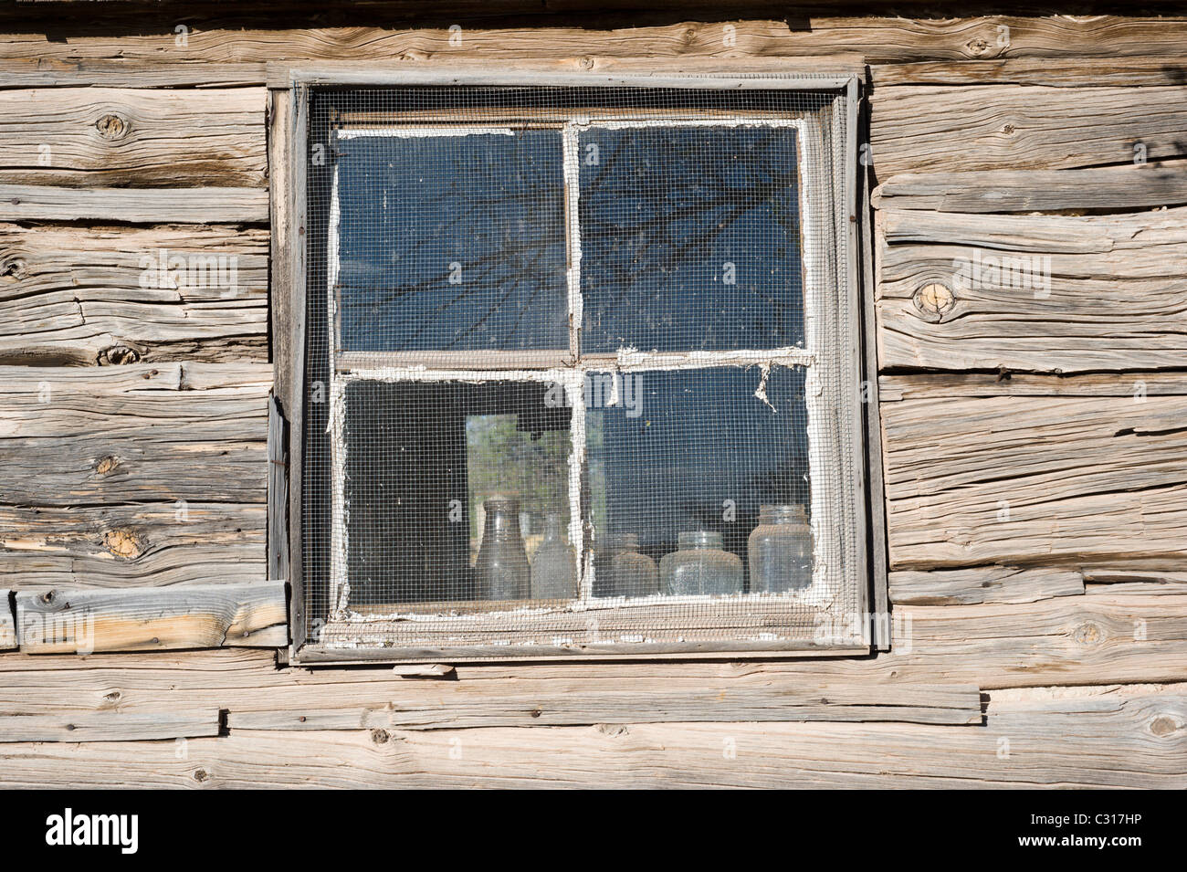 American pioneer, hand-hewn log cabin, with old bottles on the window sill in Ancho, New Mexico. - Stock Image