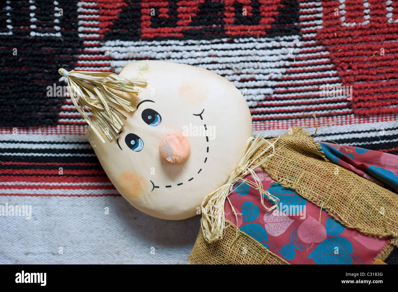 A toy doll smiling in front of an Indian blanket, New Mexico. - Stock Image