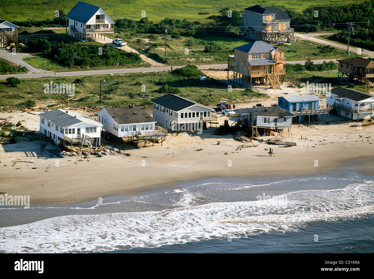 Local residents check the damage to beach front homes caused by Hurricane Floyd on Oak Island, North Carolina. - Stock Image