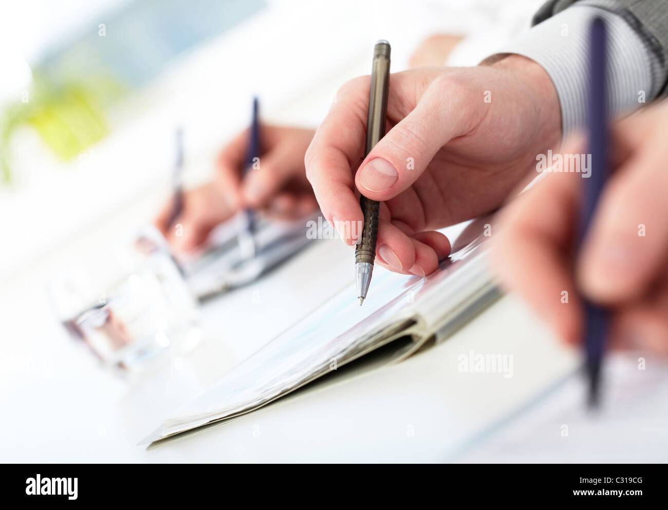 Row of human hands with pens making notes during conference - Stock Image