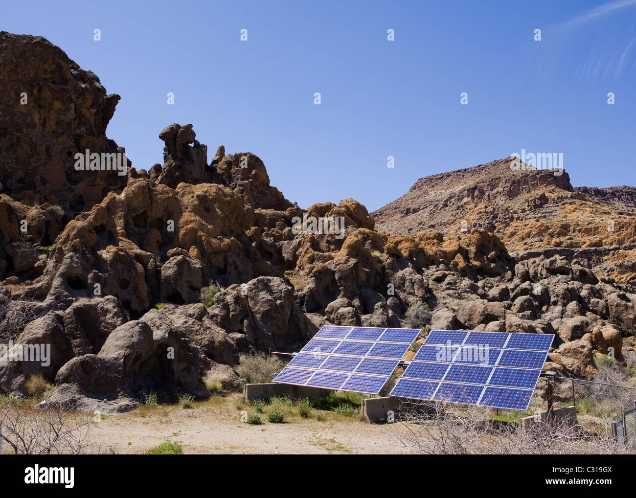 Solar panel against rocky landscape and blue sky - California USA - Stock Image
