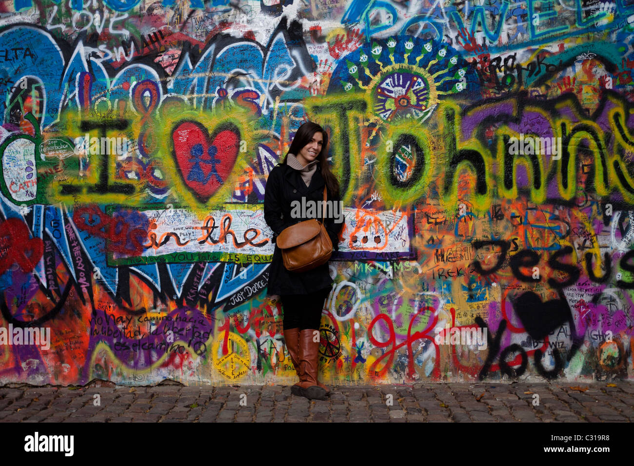 A beautiful woman has her photo taken in front of the John Lennon Wall Stock Photo