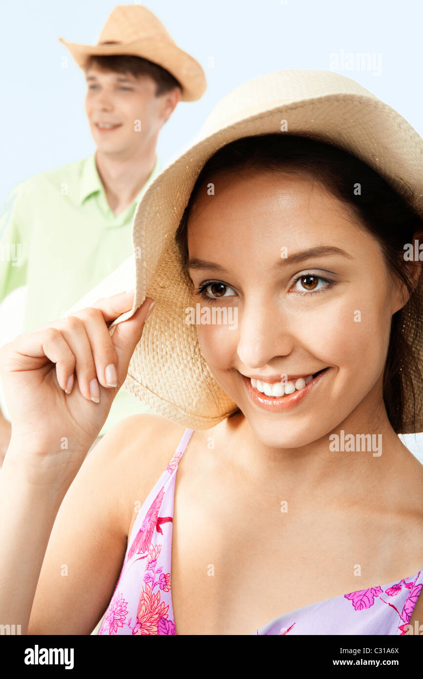 Portrait of happy girl in hat looking at camera with man on background - Stock Image