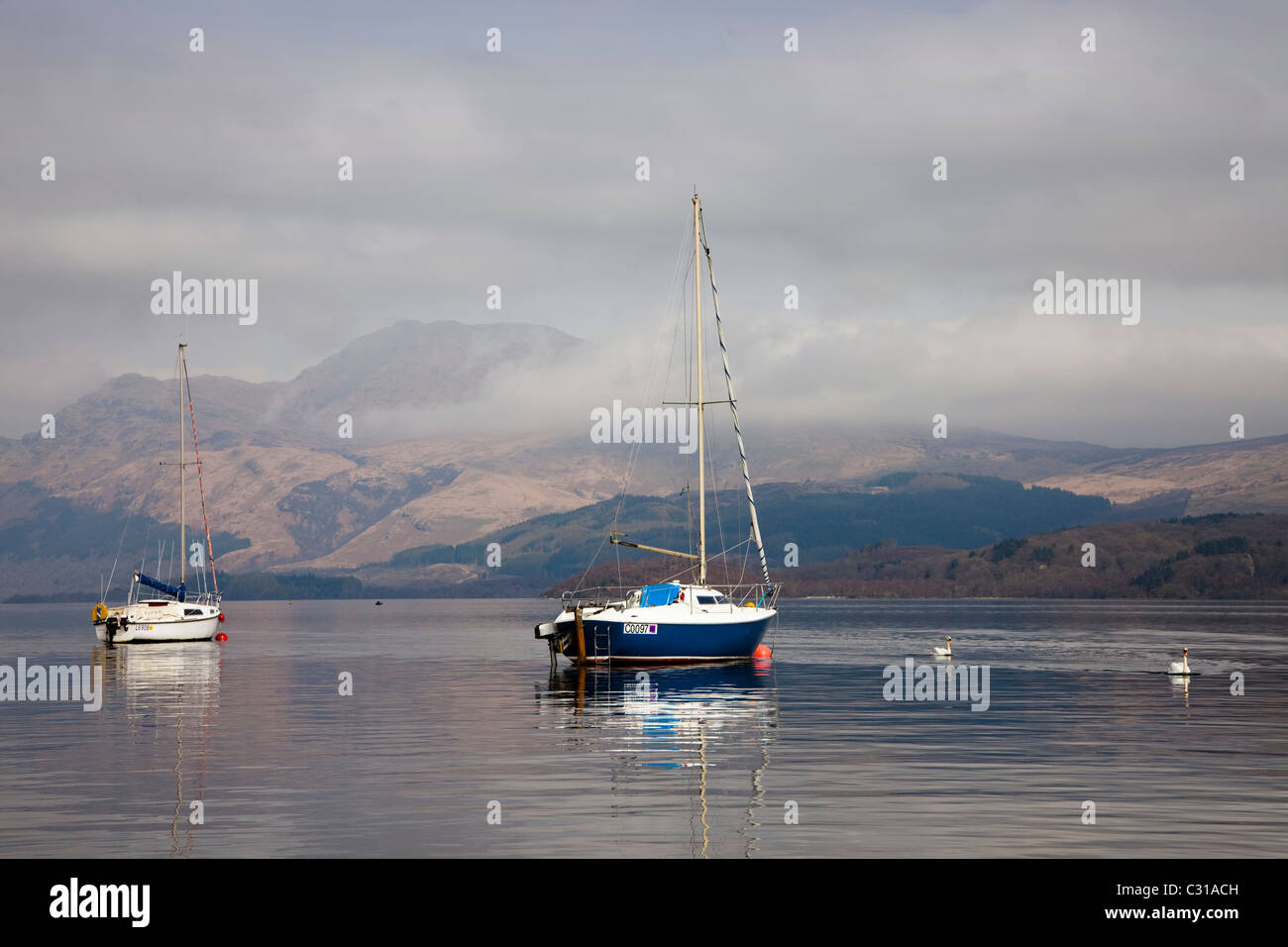 Yachts at anchor near Luss, Loch Lomond, Argyll, Scotland. Ben Lomond in the distance surrounded by clouds. - Stock Image