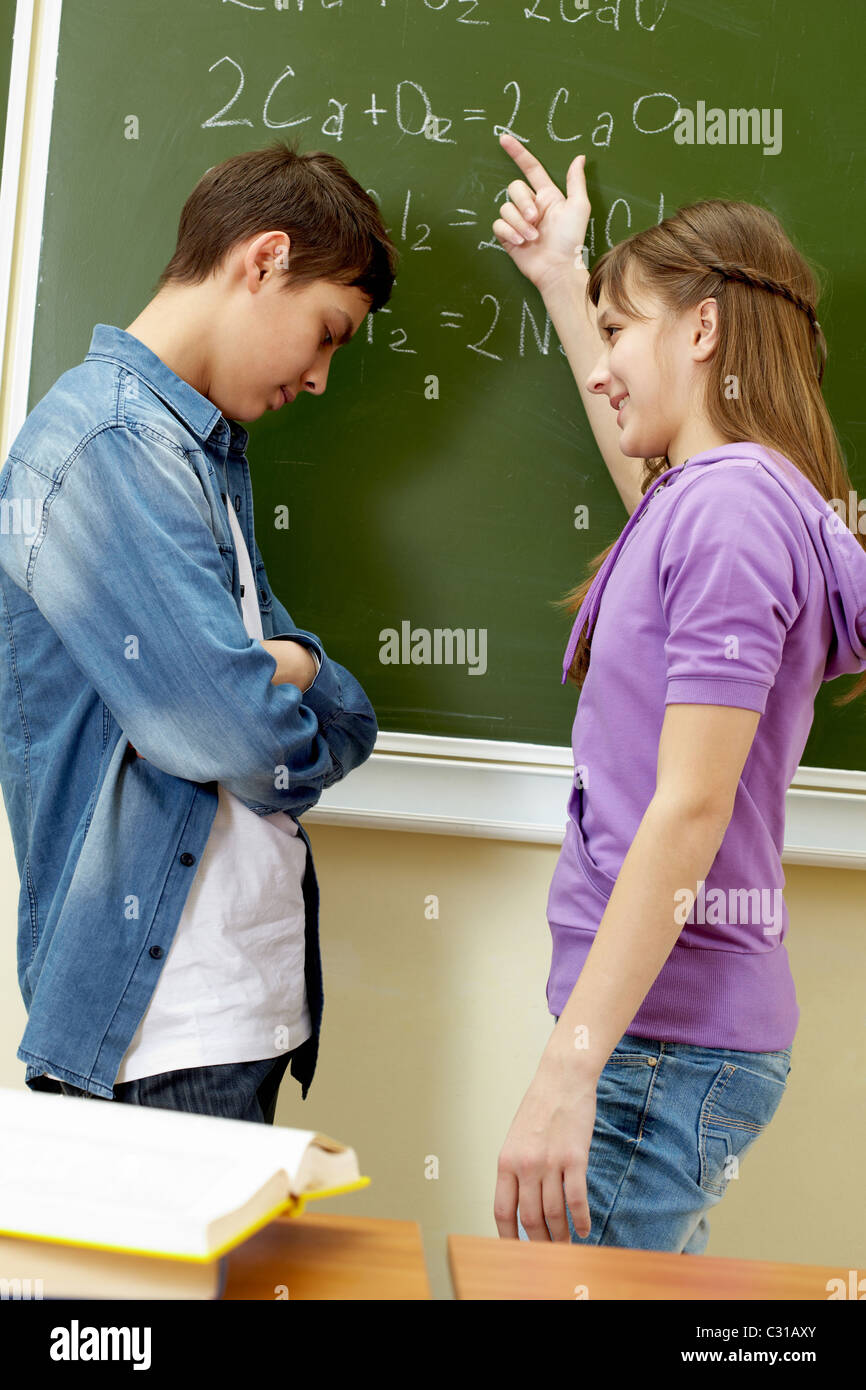 Clever girl pointing at blackboard while explaining formula to classmate - Stock Image