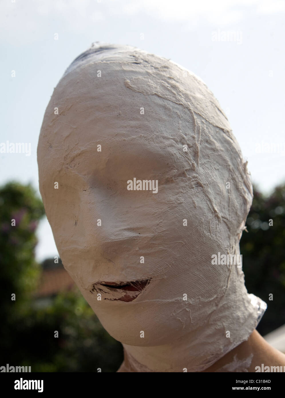 Young man head covered in white bandages as part of an art project - Stock Image