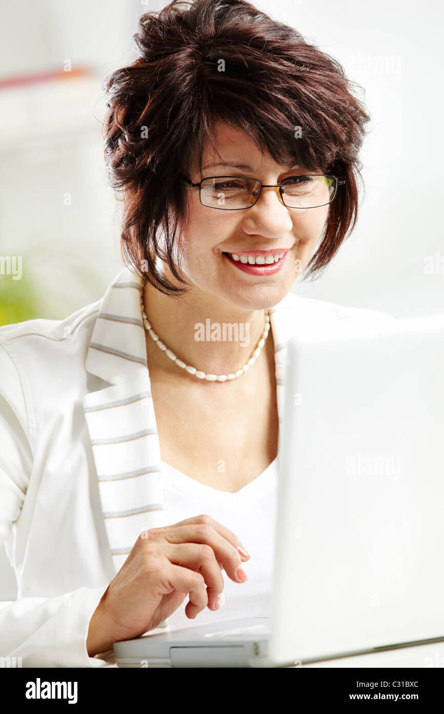 Portrait of middle-aged female typing and looking at laptop display Stock Photo